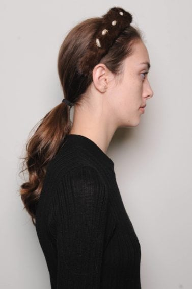 side view of a brunette model backstage at the Altuzarra fashion show wearing a black top with her hair pulled back into a ponytail and a headband
