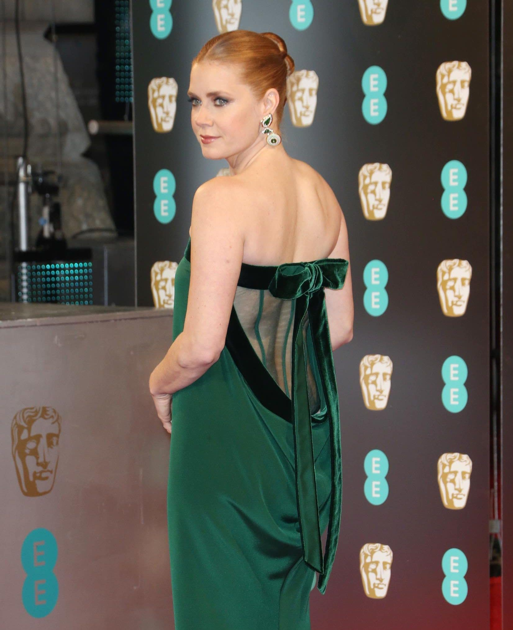 Amy Adams at the baftas 2017 in a mesh green dress with her red hair styled into a ballerina bun