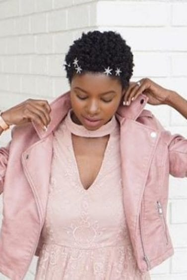close up shot of woman with fluffed out short natural hair, wearing stars in her hair and all pink outfit, posing outside