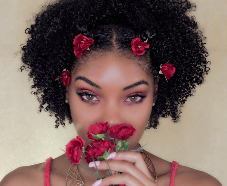 natural hairstyles for short hair: shot of woman with bantu knots and short natural hair with flowers in them