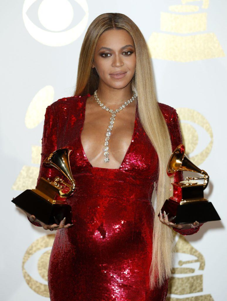 pregnant beyonce on the red carpet in a glittery red sequin dress holding two grammy awards with really long straight blonde hair