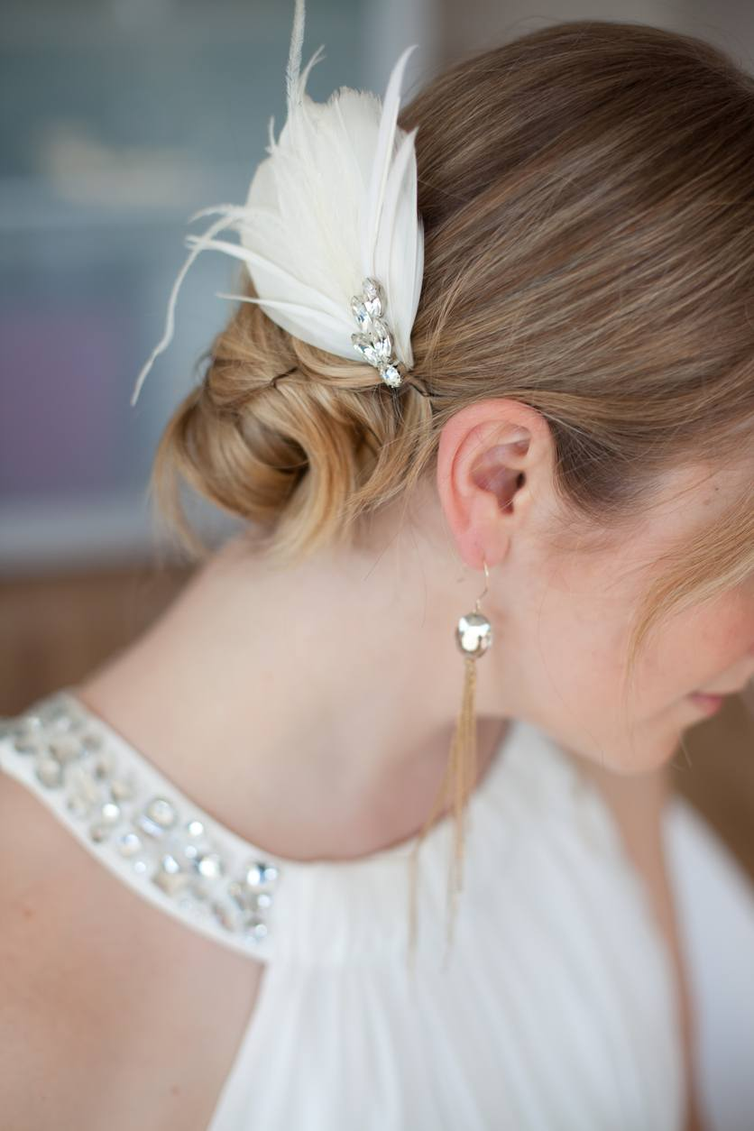 blonde bride with halterneck white dress and a bun hairstyle with feather accessory