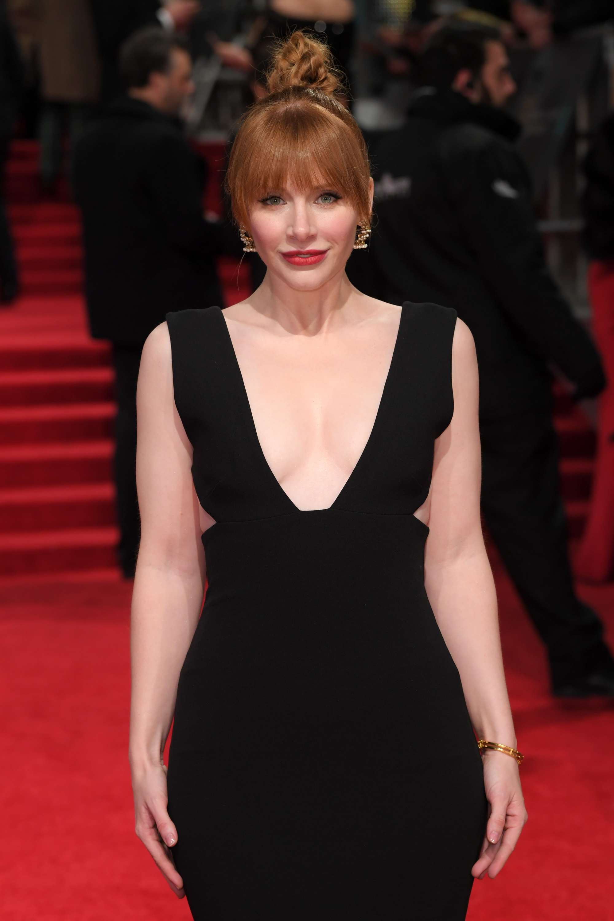 Bryce Dallas Howard wearing a plunging black gown with her red hair styled into a top knot updo