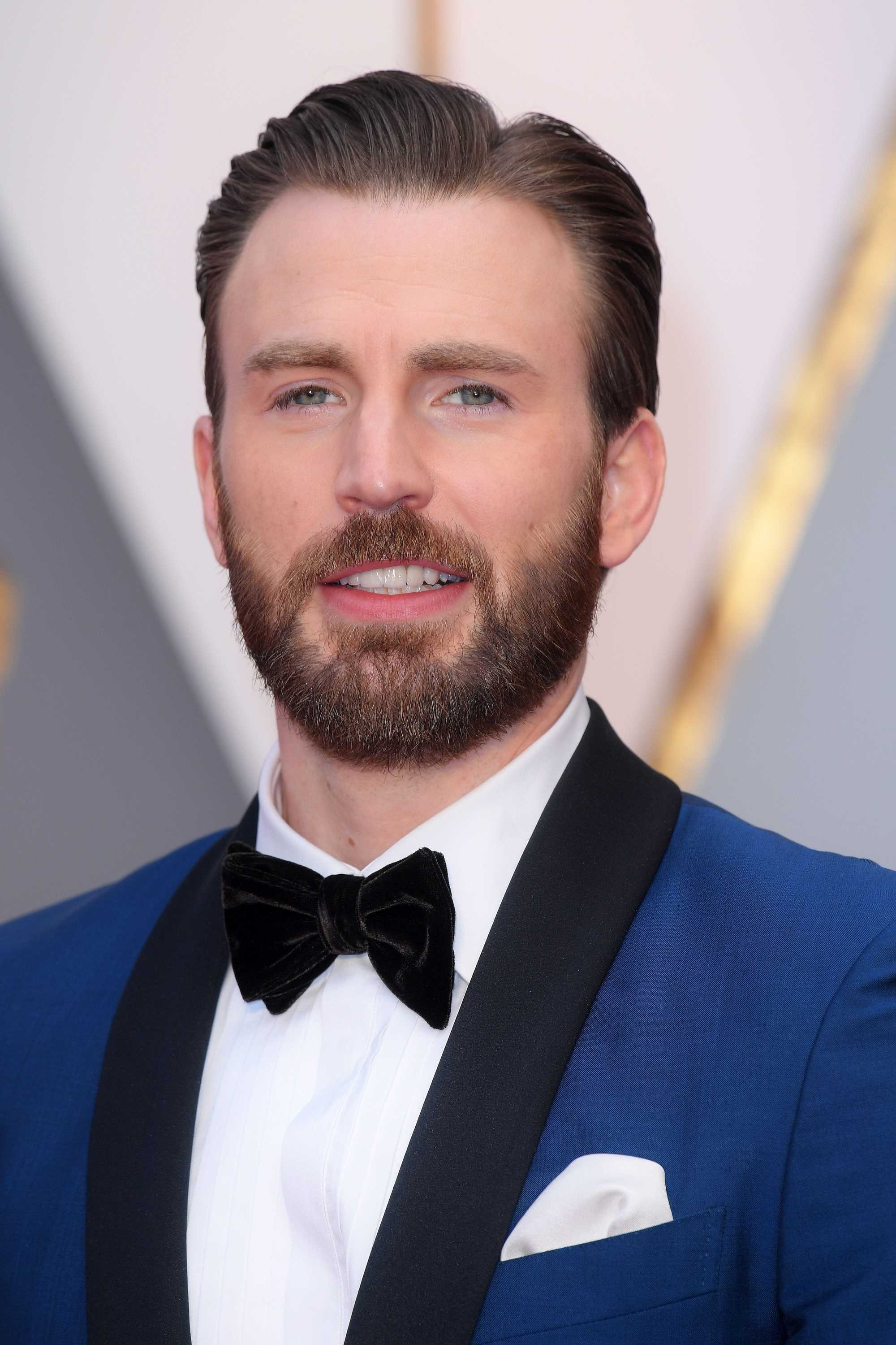 chris evans with slick side part and blue suit with bow tie