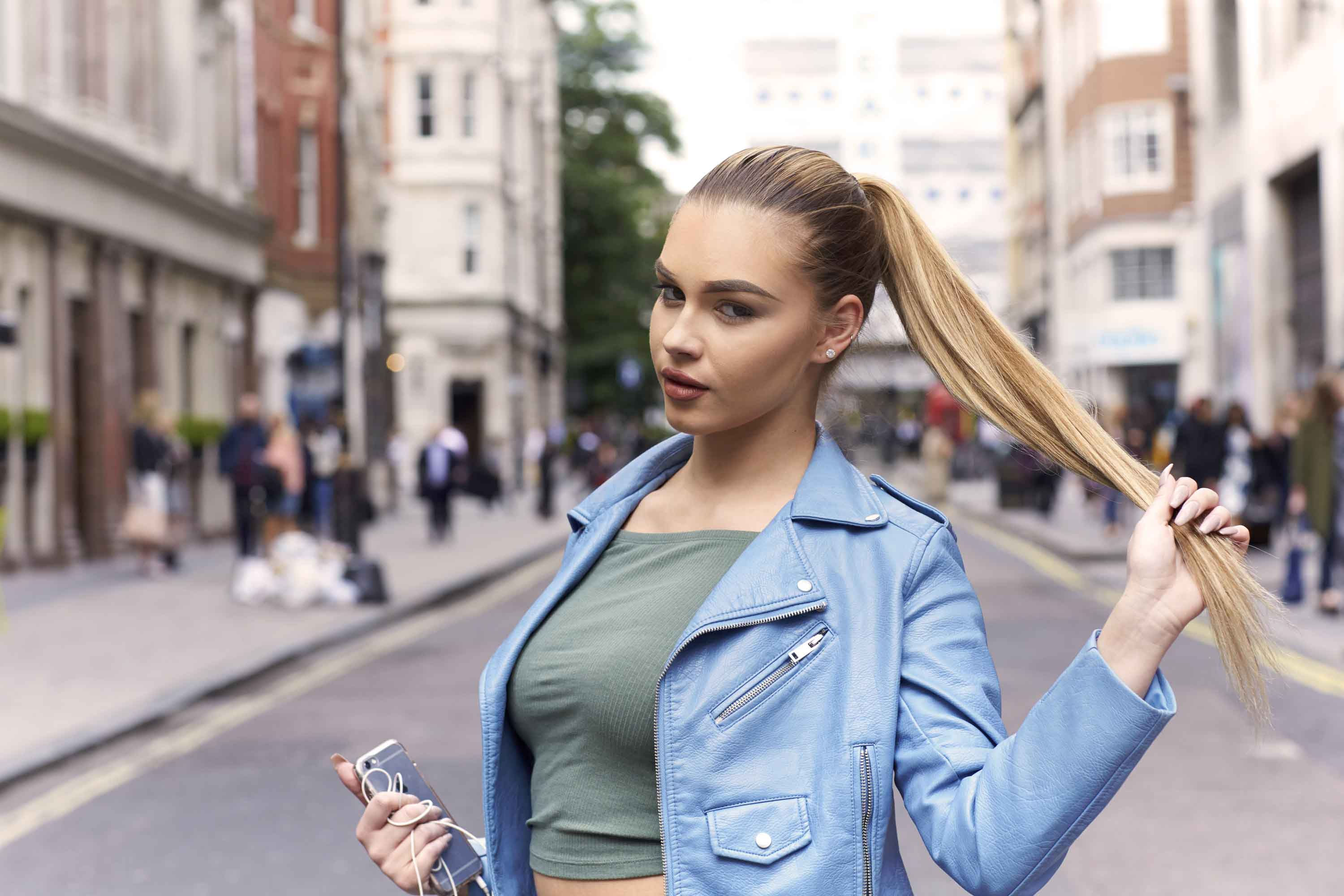Club hairstyles: Image of a blonde woman with a sleek high ponytail wearing a blue leather jacket and khaki green top, standing in the middle of the road
