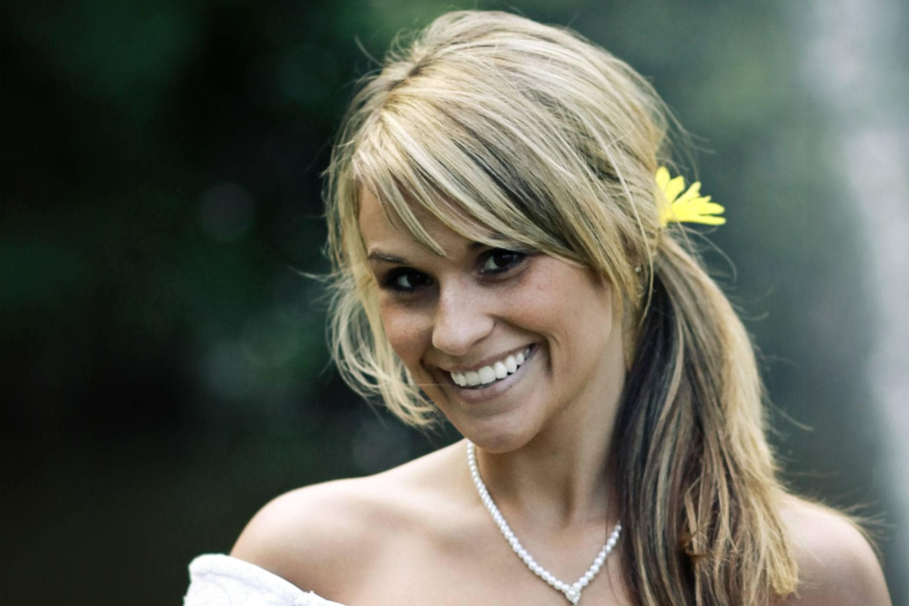 blonde bride wearing a white dress and necklace with her hair in a side ponytail with a flower hair accessory