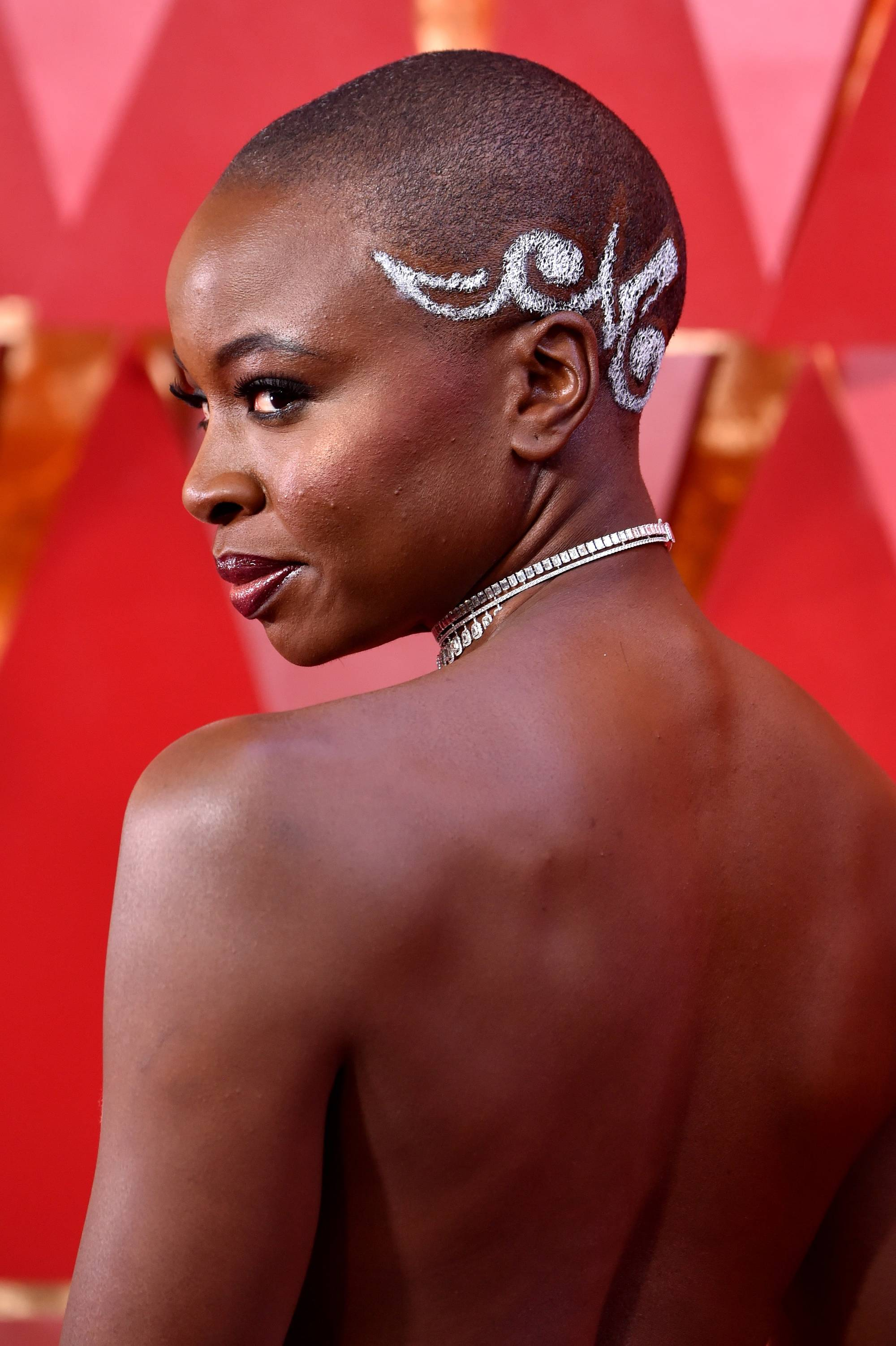 black panther actress danai gurira at the oscars 2018 with a spray painted metallic white design on her buzz cut