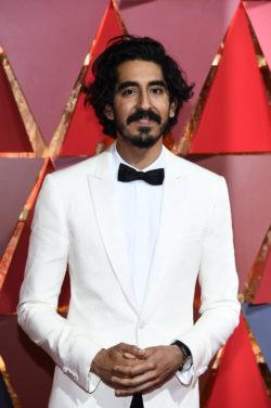 lions actor dev patel with curly hair and white suit and black bow tie
