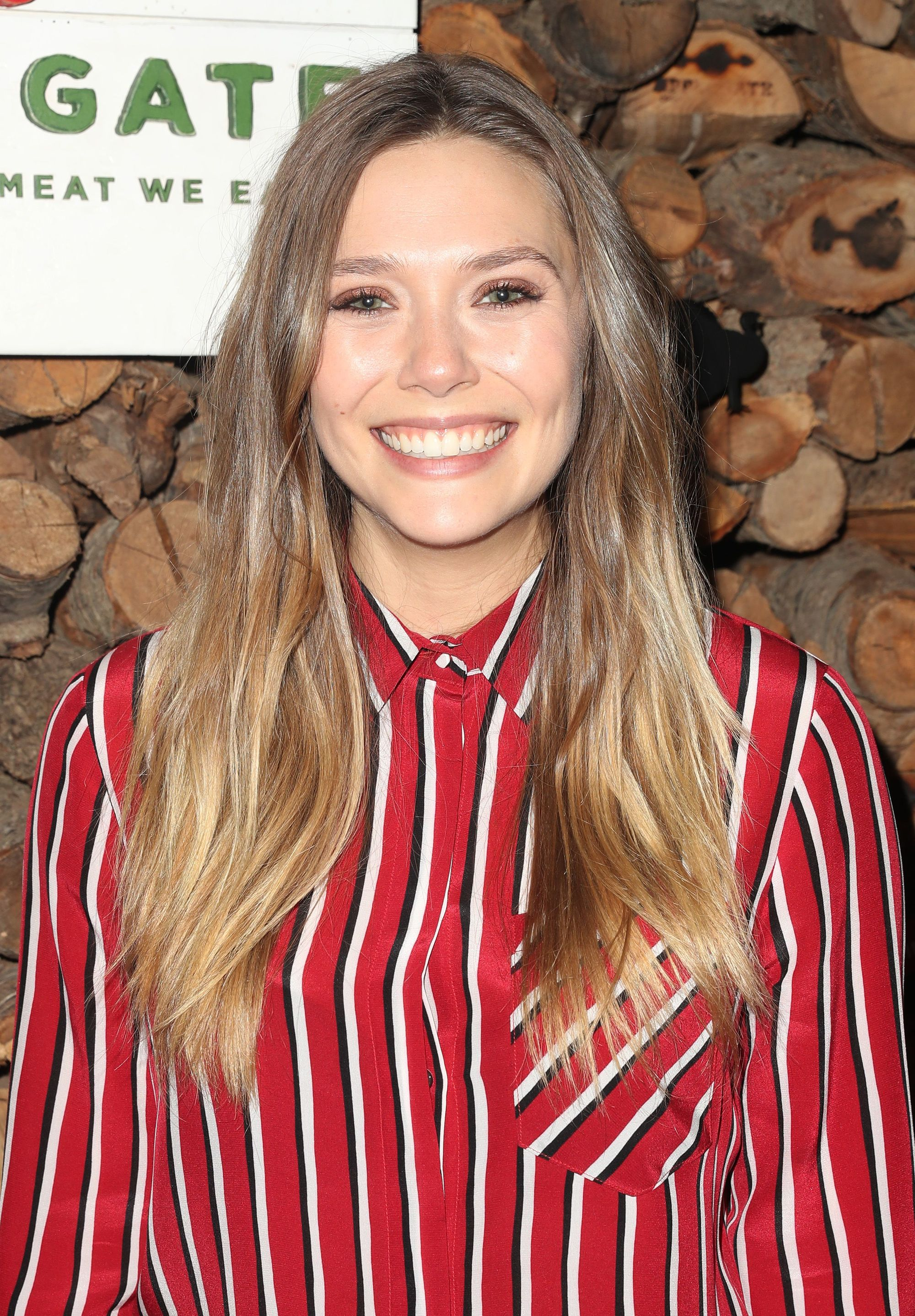 Elizabeth Olsen wearing a striped red shirt with long bronde hair colour