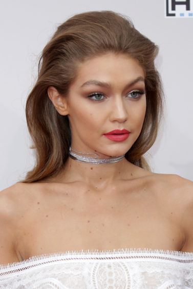 gigi hadid wearing strapless dress and red lipstick with relaxed quiff rockabilly hairstyle