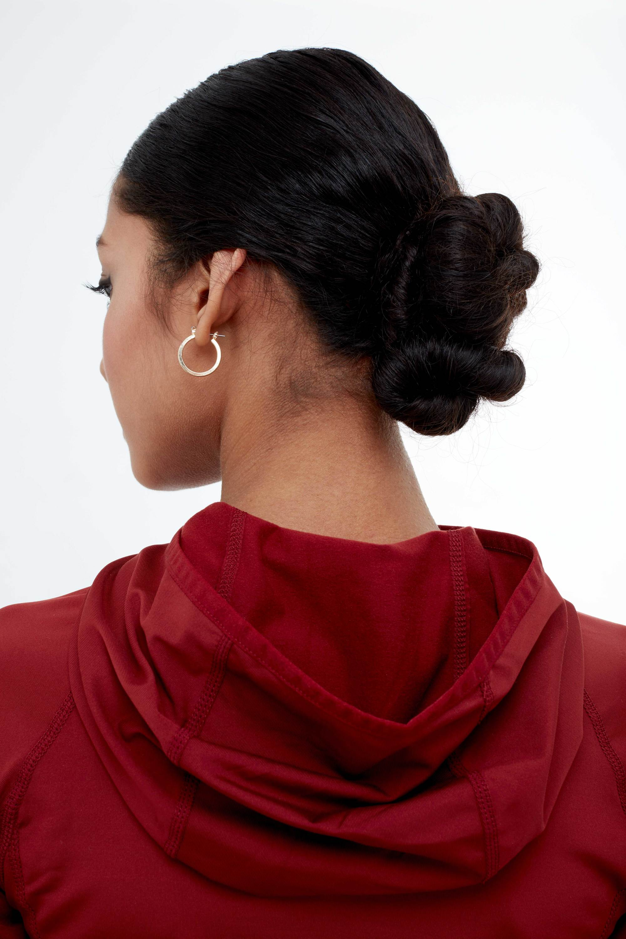 Backshot of a woman with dark brown hair styled into a low twisted bun, wearing a red workout outfit with a hoop earring in the All Things Hair studio