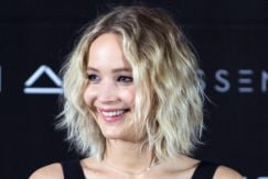 jennifer lawrence on the red carpet in a black v neck dress with blonde curly short bob hair
