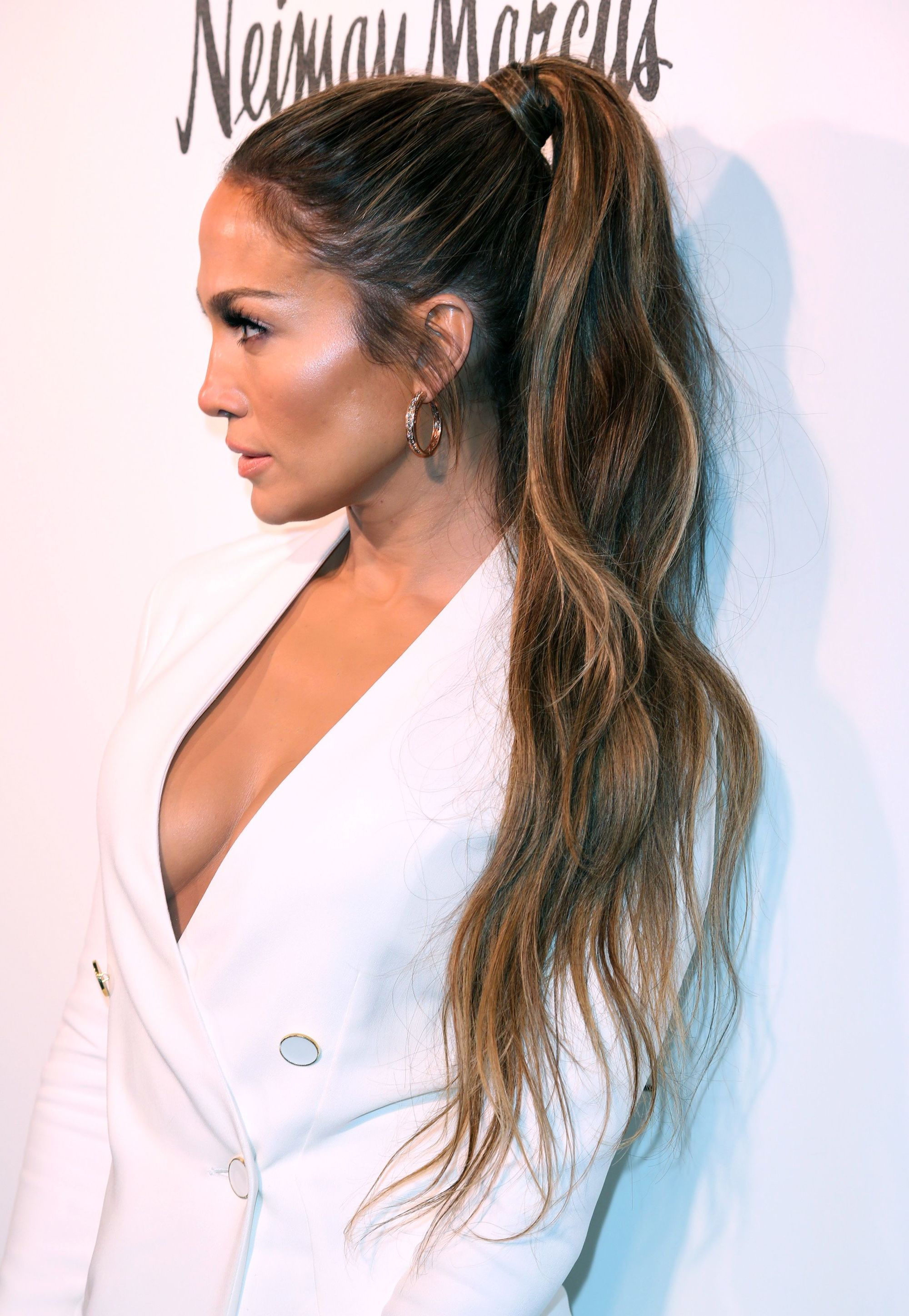 Jennifer Lopez wearing a white blazer with a super long blonde ombre ponytail