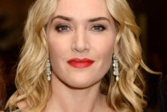 kate winslet in a black v neck dress with shoulder length blonde wavy hair