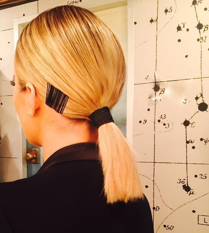 Gym hairstyles for thick hair: Close-up back view of Khloe Kardashian with blonde hair in a low sleek ponytail with bobby pin details