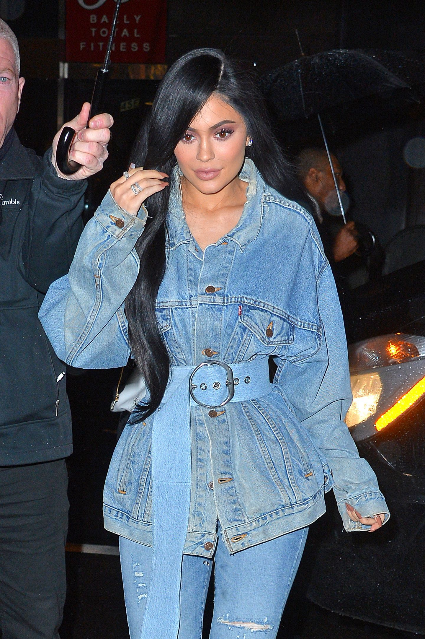 kylie jenner wearing a denim jacket and jeans with super long wavy black hair