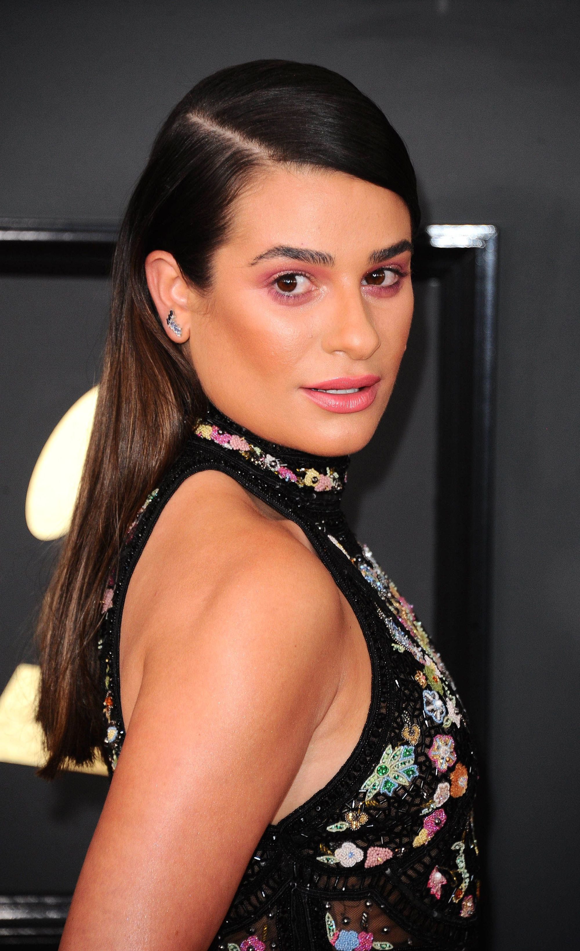 Lea Michele wearing floral halterneck black dress with her hair in a sleek side parting