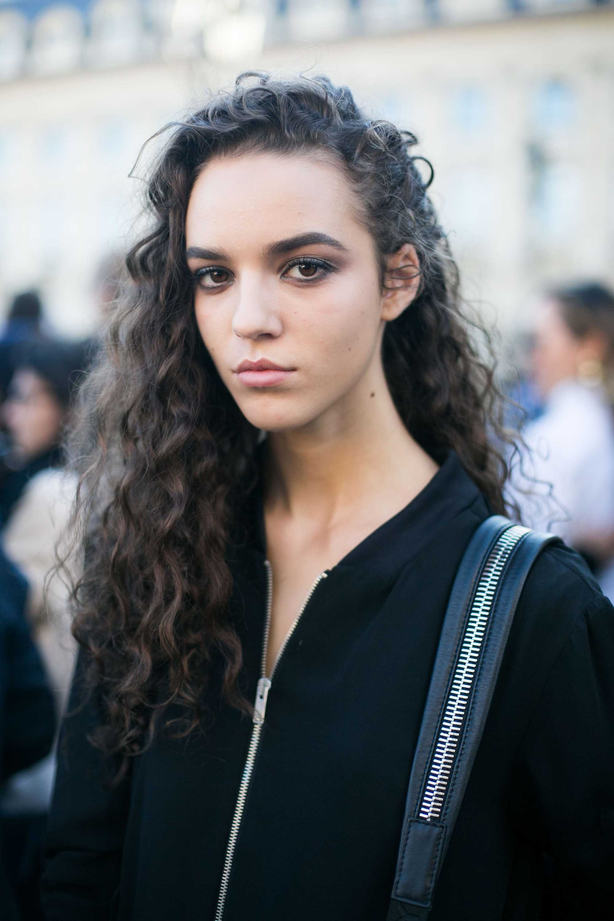 model with long curly hair wearing black