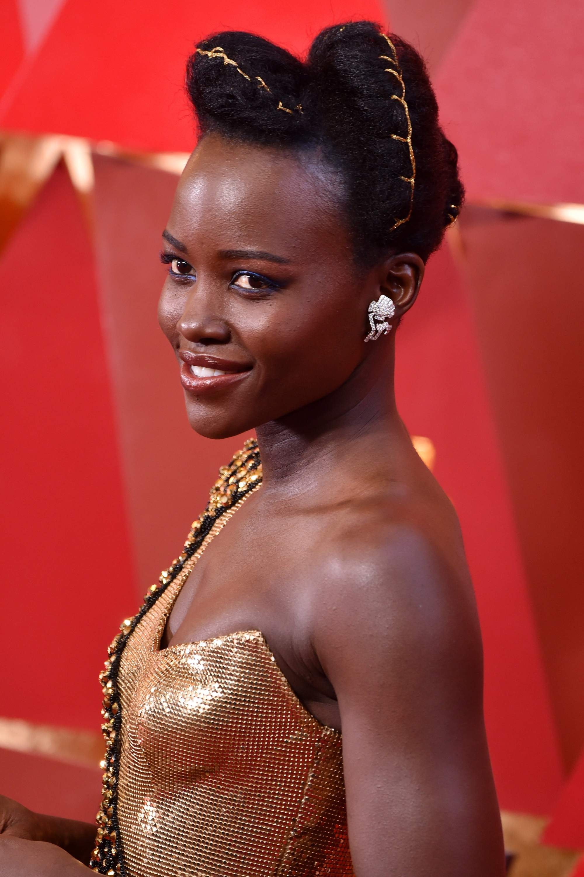 black panther actress lupita nyongo at the oscars 2018 with her hair in an updo with gold thread running through