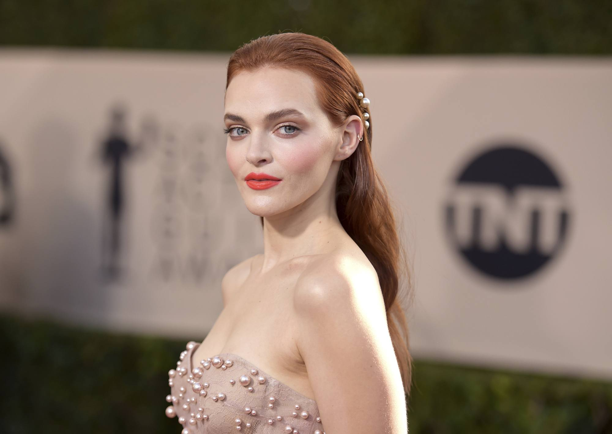 close up shot of Madeline brewer with slicked back hair with pearls in it, wearing pearly dress