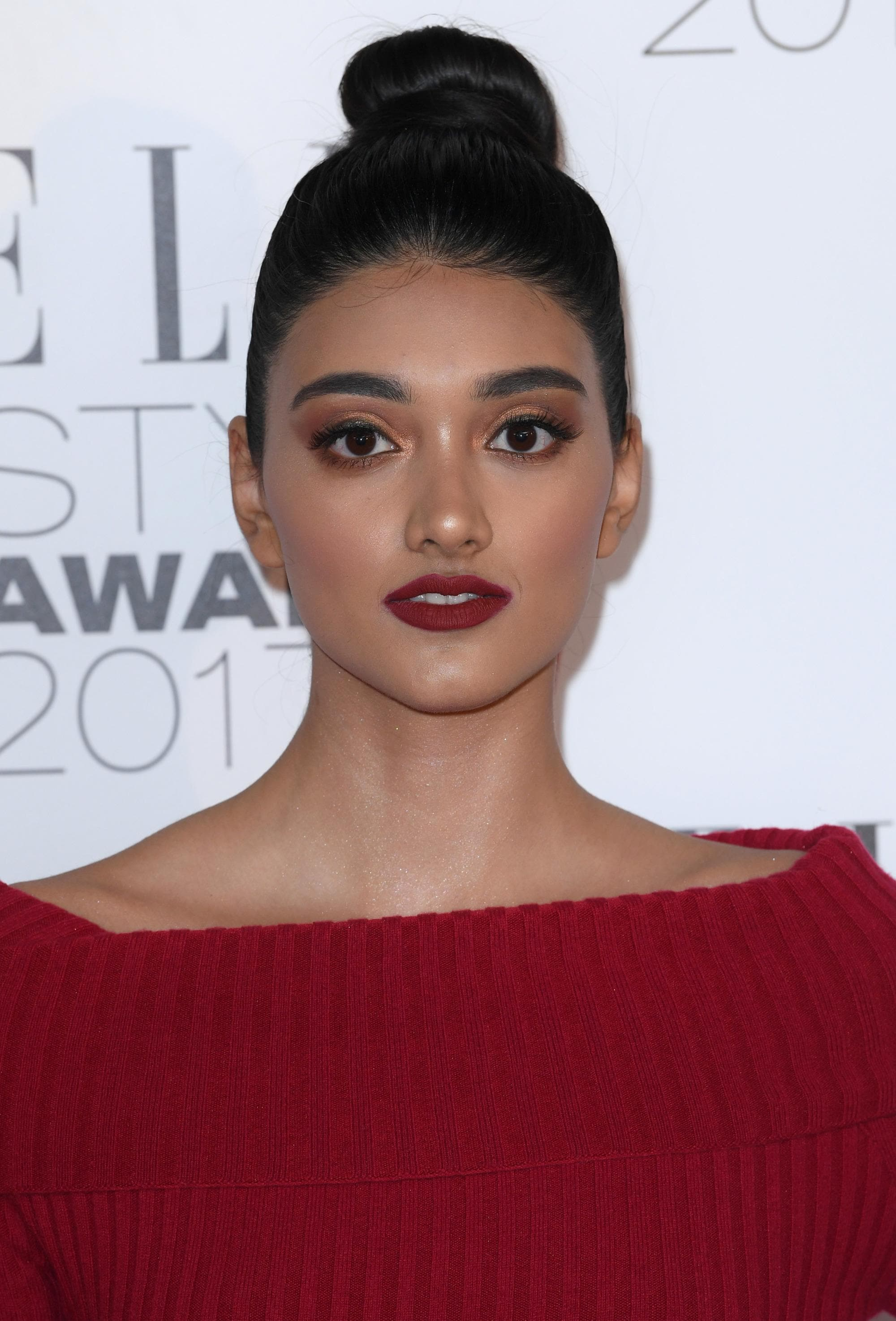 Neelam Gill at the elle style awards in an off the shoulder red dress with her dark hair styled into a top knot bun