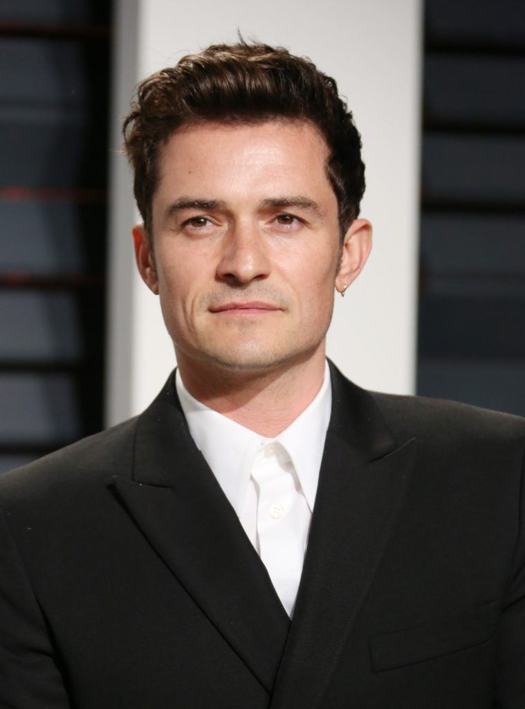 orlando bloom on the oscars 2017 red carpet wearing a black suit and white shirt with his dark brown hair worn in a quiff