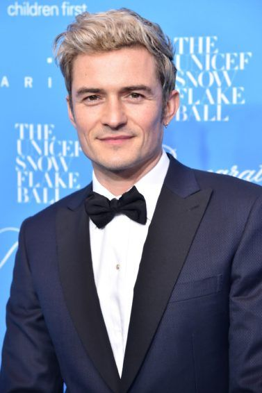 orlando bloom on the red carpet wearing a navy suit with a white shirt and a bow tie and his blonde hair worn in a quiff
