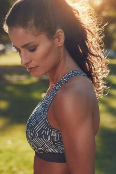 model in gym wear in the park with ponytail hairstyle