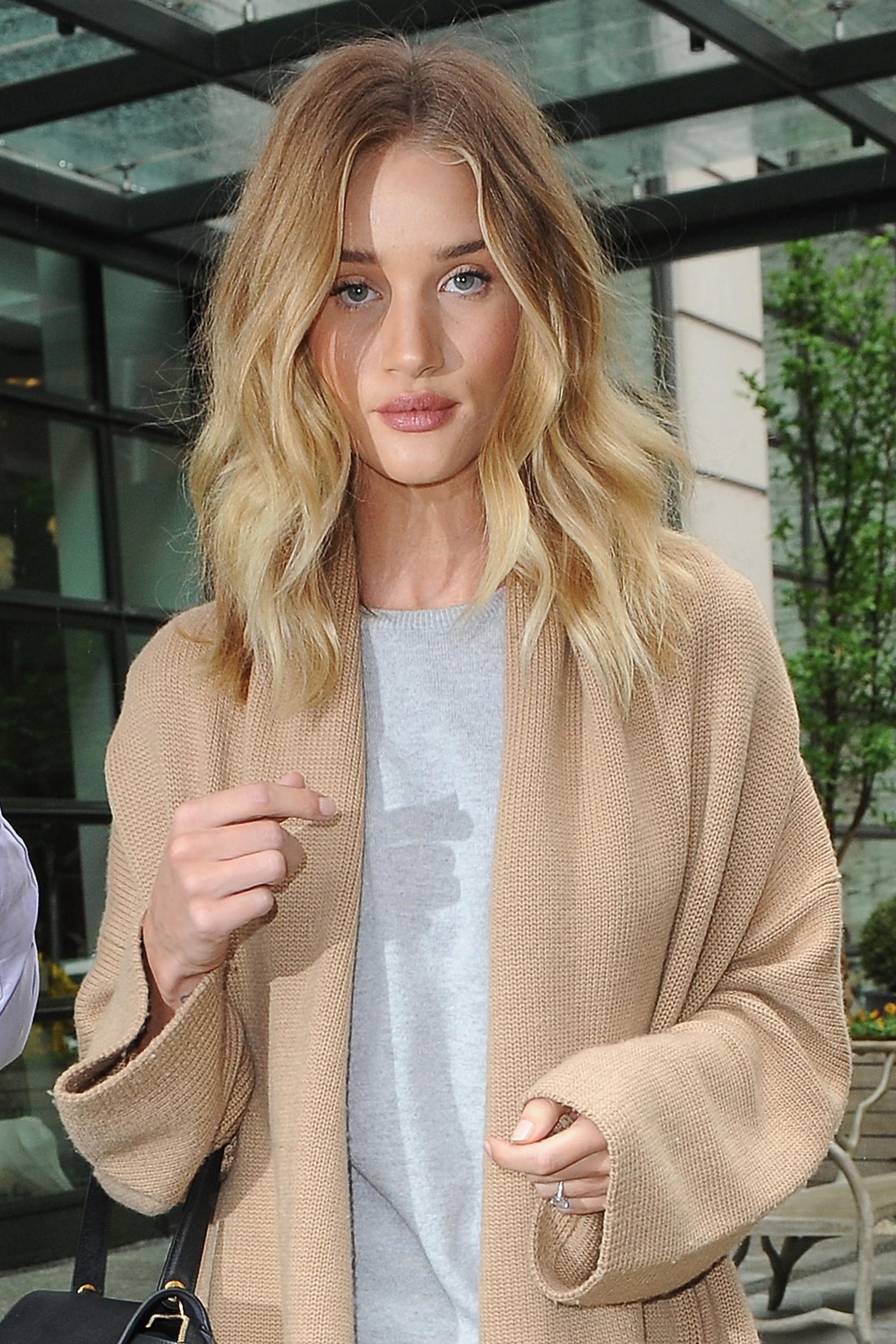 rosie huntington-whiteley wearing a grey top and camel coat with a bronde lob hairstyle