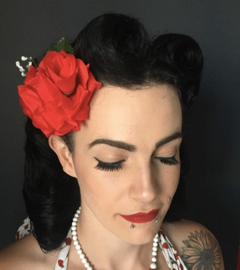 Club hairstyles: Close-up of a woman with dark brown black hair in a vintage victory roll updo with a big red flower clip