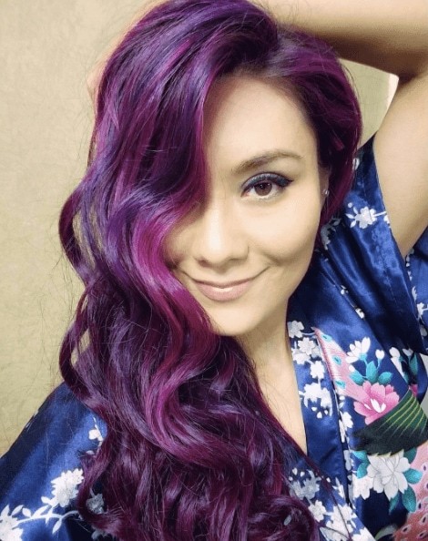Club hairstyles: Woman with long wavy purple highlighted hair swept over one shoulder