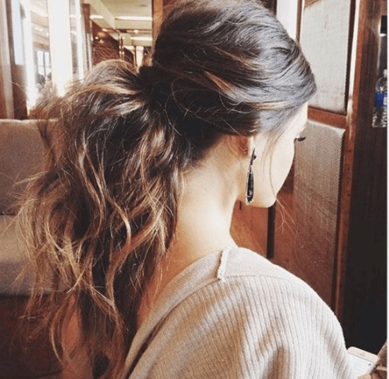 Club hairstyles: Back view of a voluminous wavy brunette ponytail