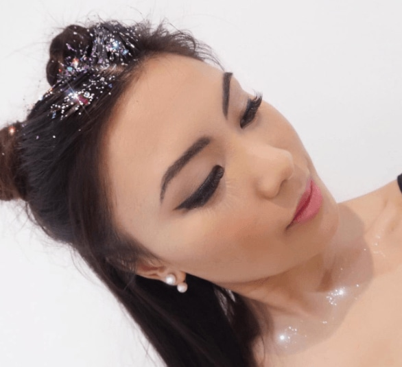Club hairstyles: Front view image of a girl with long dark hair in two space buns with a glitter parting - club hairstyles