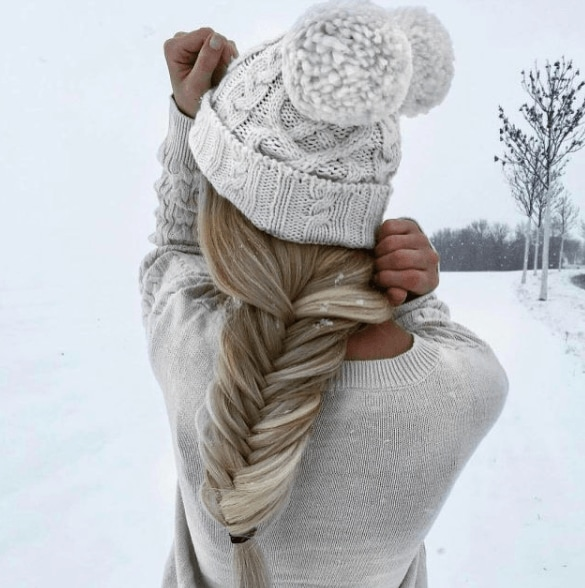 back view of a woman in the snow with a fishtail braid in her long blonde hair wearing a bobble hat