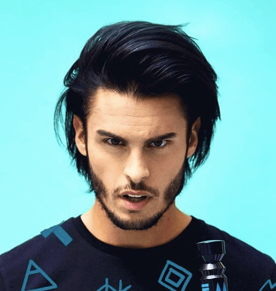 front view image of a man with longer dark hair in a quiff hairstyle