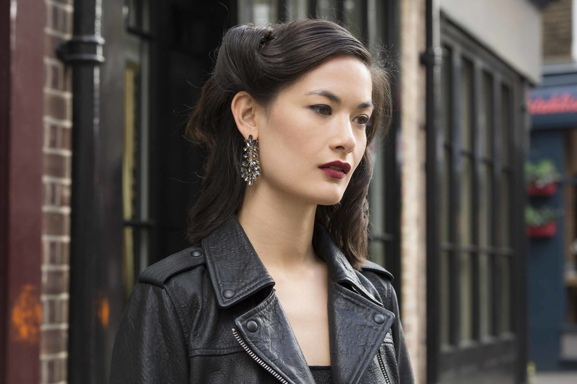 close up shot of woman with brown hair fashioned in a wavy glam roll. wearing black jacket and swanky earrings