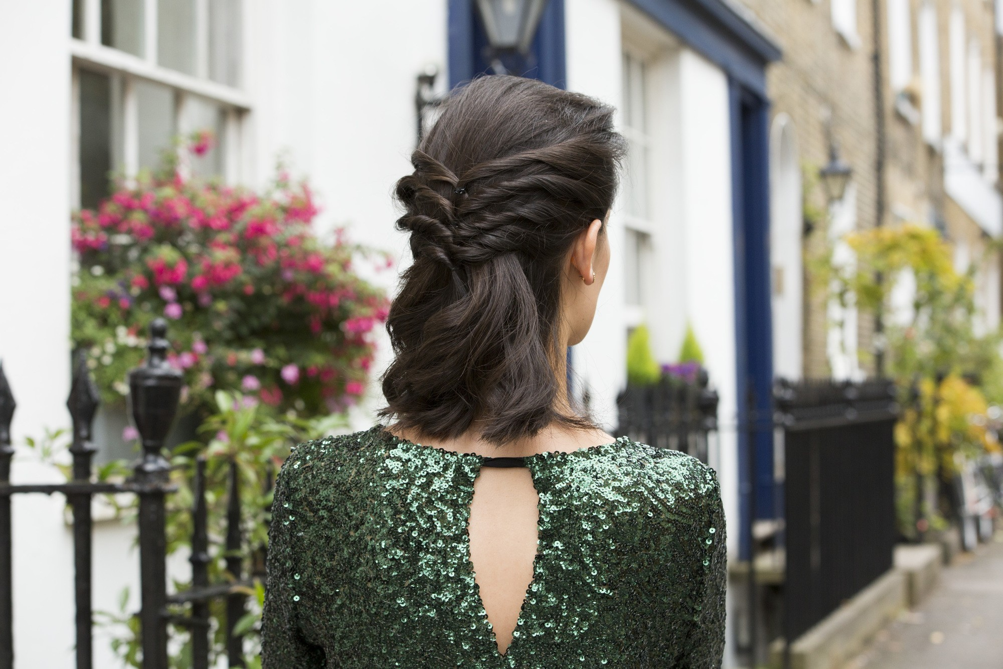 close up shot of woman with twisted half up half down hairstyle, wearing glittering dress and posing outside