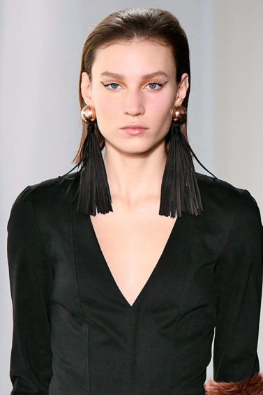 brunette model on the runway with a long bob hairstyle worn sleek, wearing a black outfit and big statement earrings