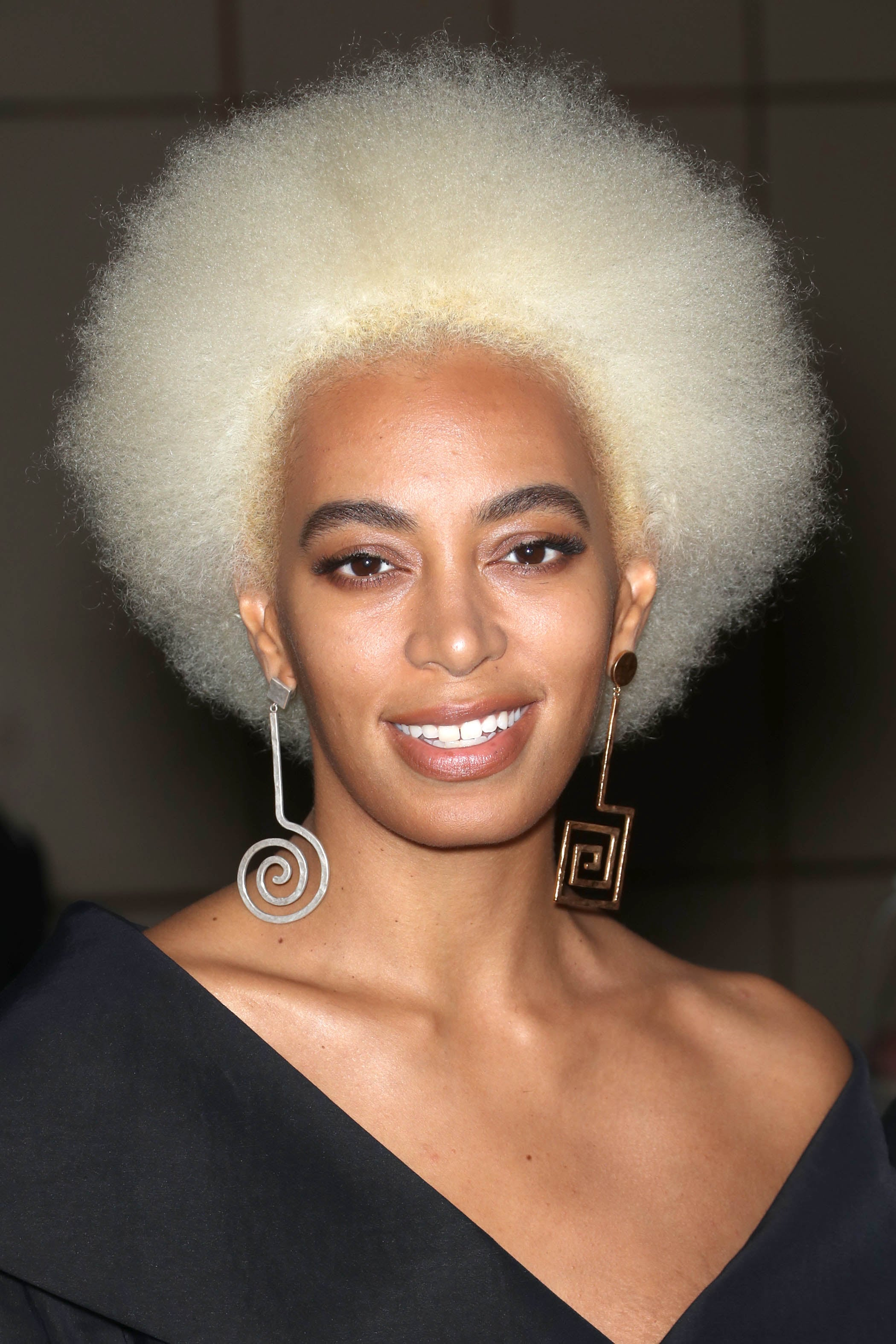 natural hairstyles for short hair: close up shot of solange with blonde afro hairstyle, wearing statement earrings and black outfit, posing on the red carpet
