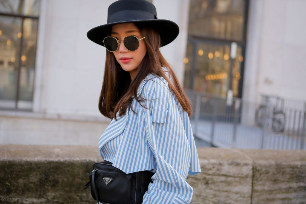 Asian woman stood outside wearing a blue shirt, sunglasses and a hat over her brown hair