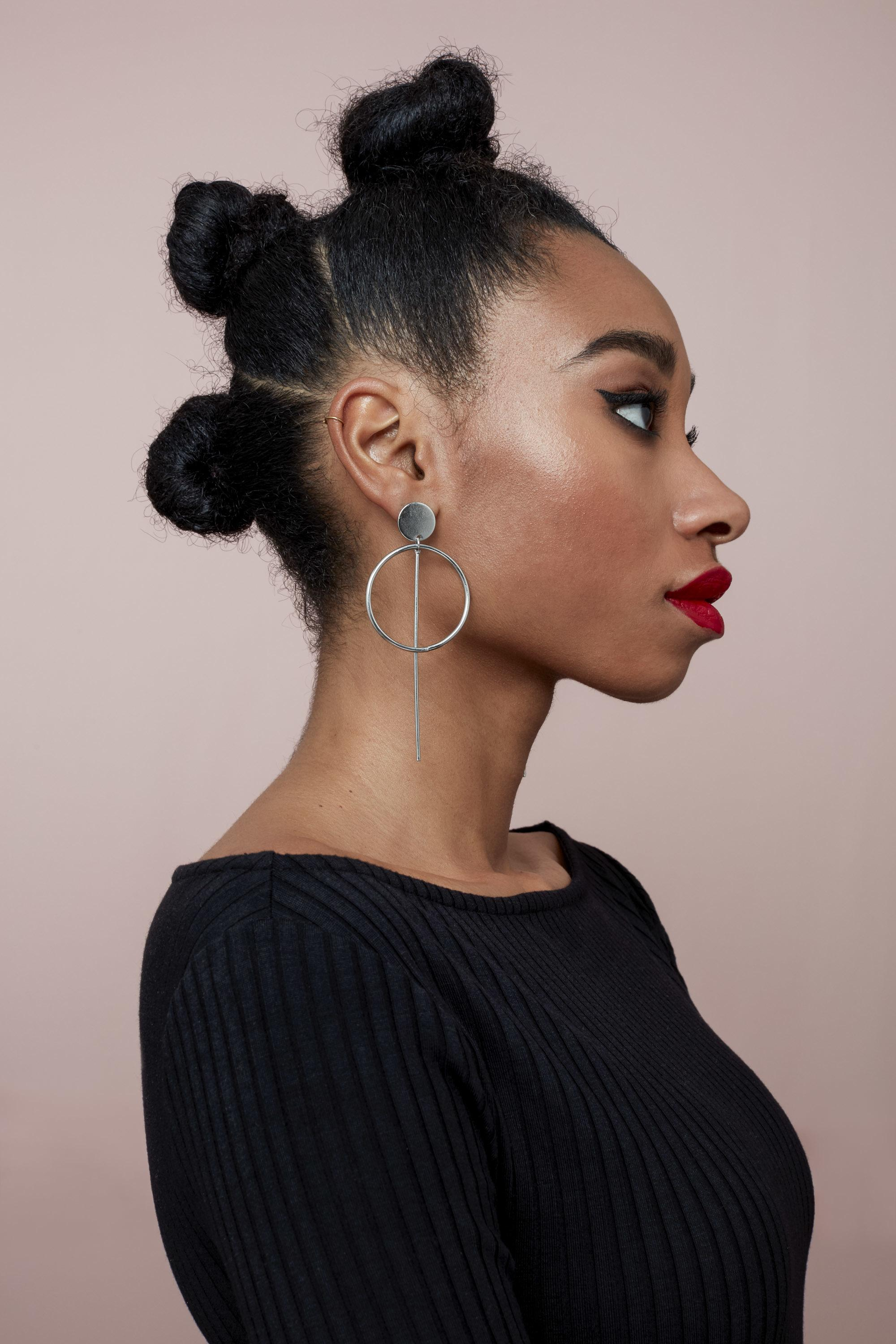 Natural hairstyles for Valentine's Day: Shot of model with triple bantu knot buns, wearing dangling earring and red lipstick, wearing all black in the All Things Hair UK Studio