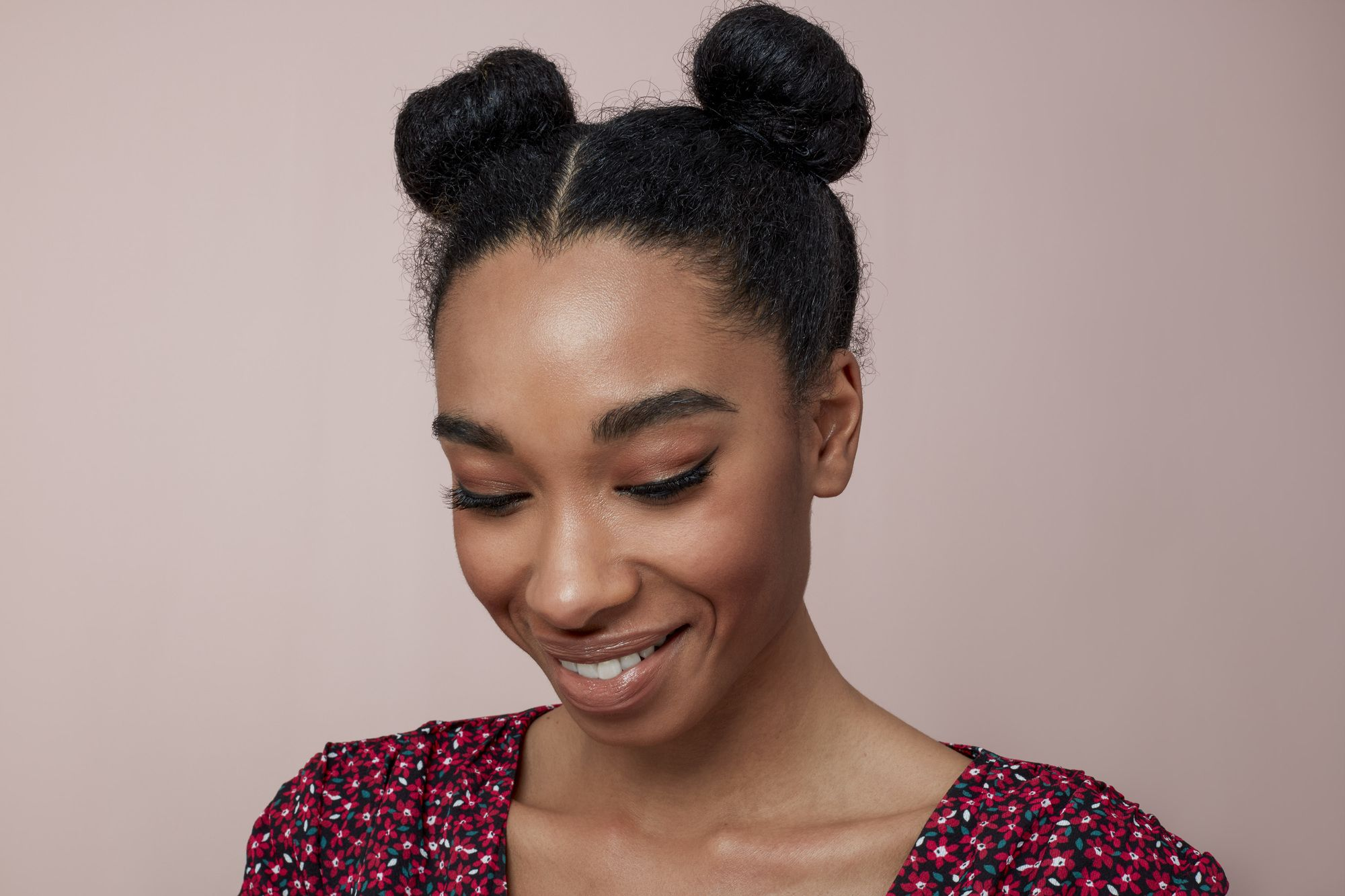 Natural hairstyles for Valentine's Day: Woman with dark brown hair styled into space natural space buns