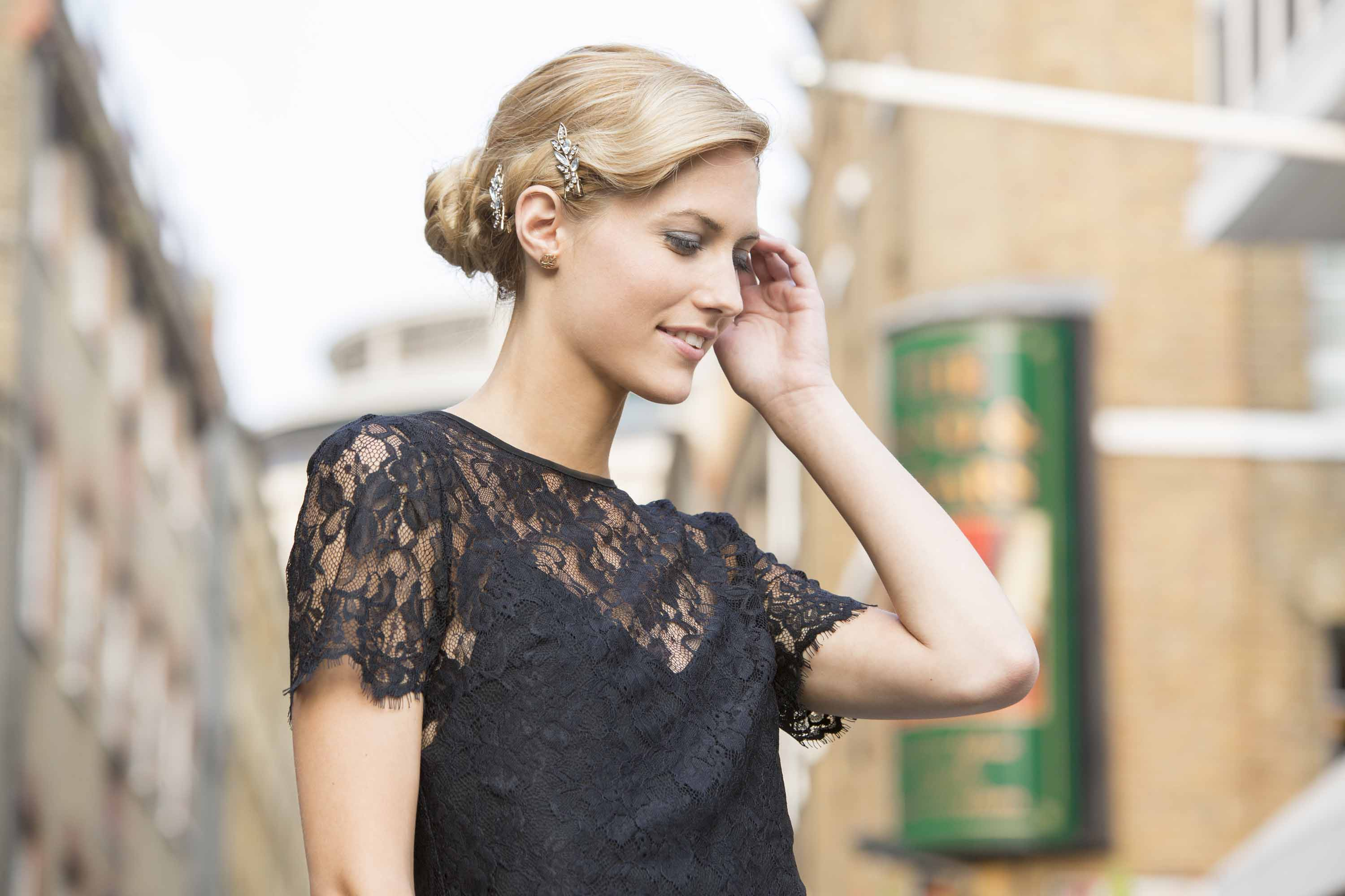 close up shot of woman with blonde hair vintage updo, wearing black lace top and posing outside