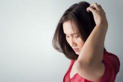woman in red top touching and inspecting her scalp