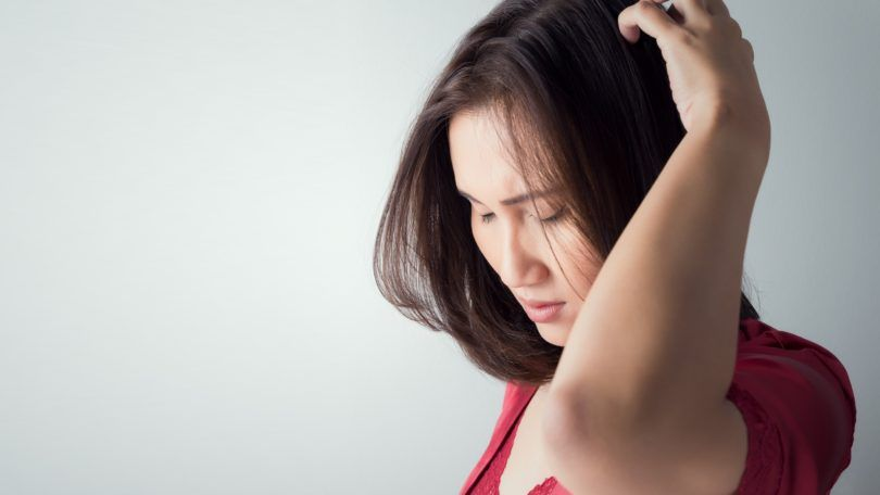 itchy scalp dry scalp woman in red top touching and inspecting her scalp