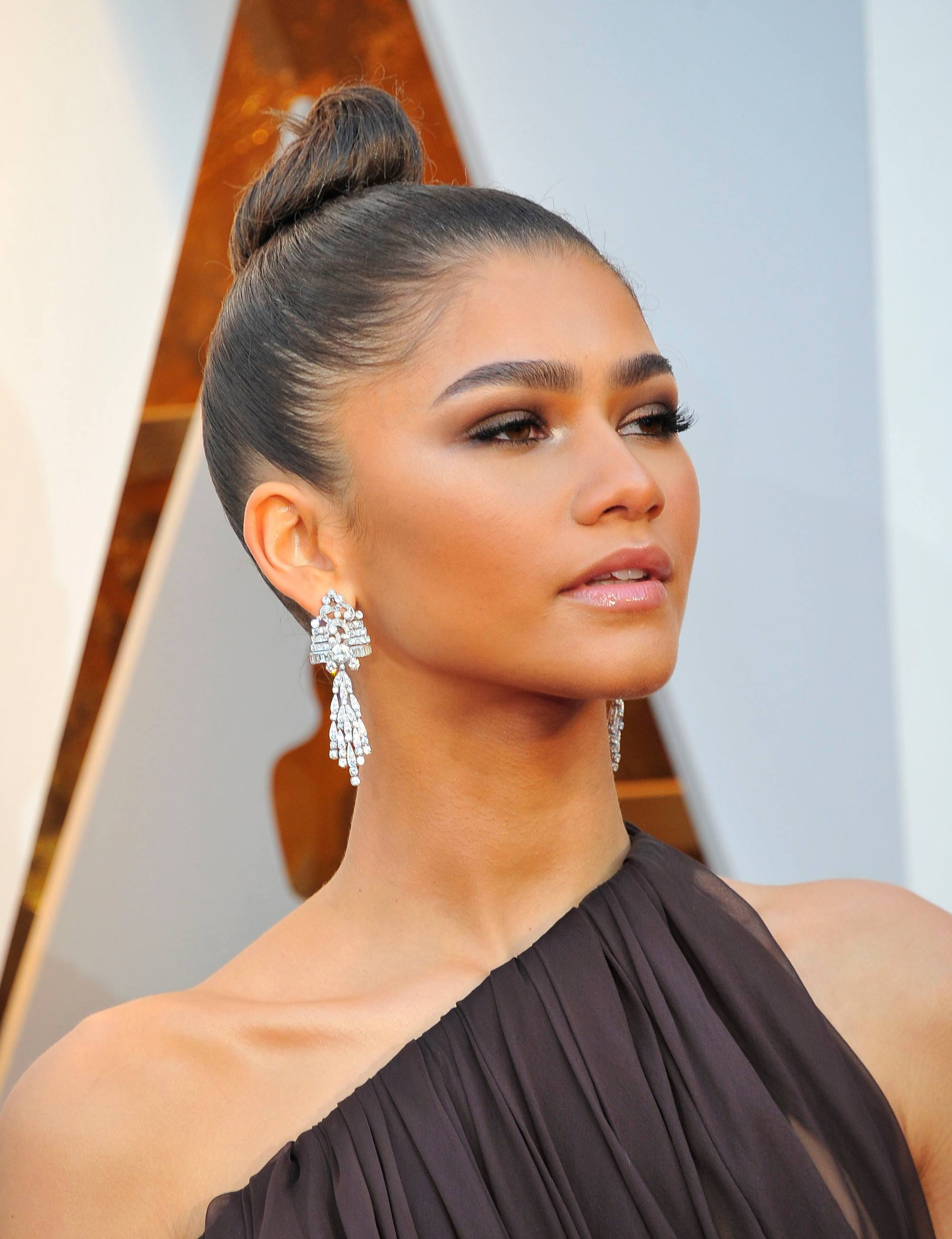 actress zendaya at the 2018 oscars wearing a one shoulder dress with her hair in a slick top knot