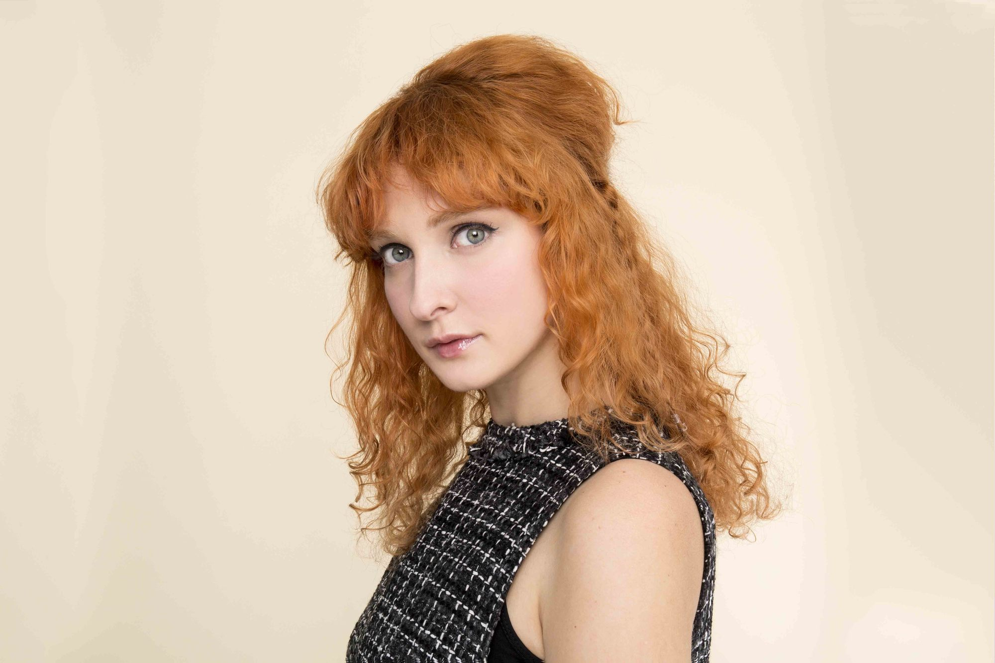 Curly redhead young woman with fringe and half up bouffant hairstyle