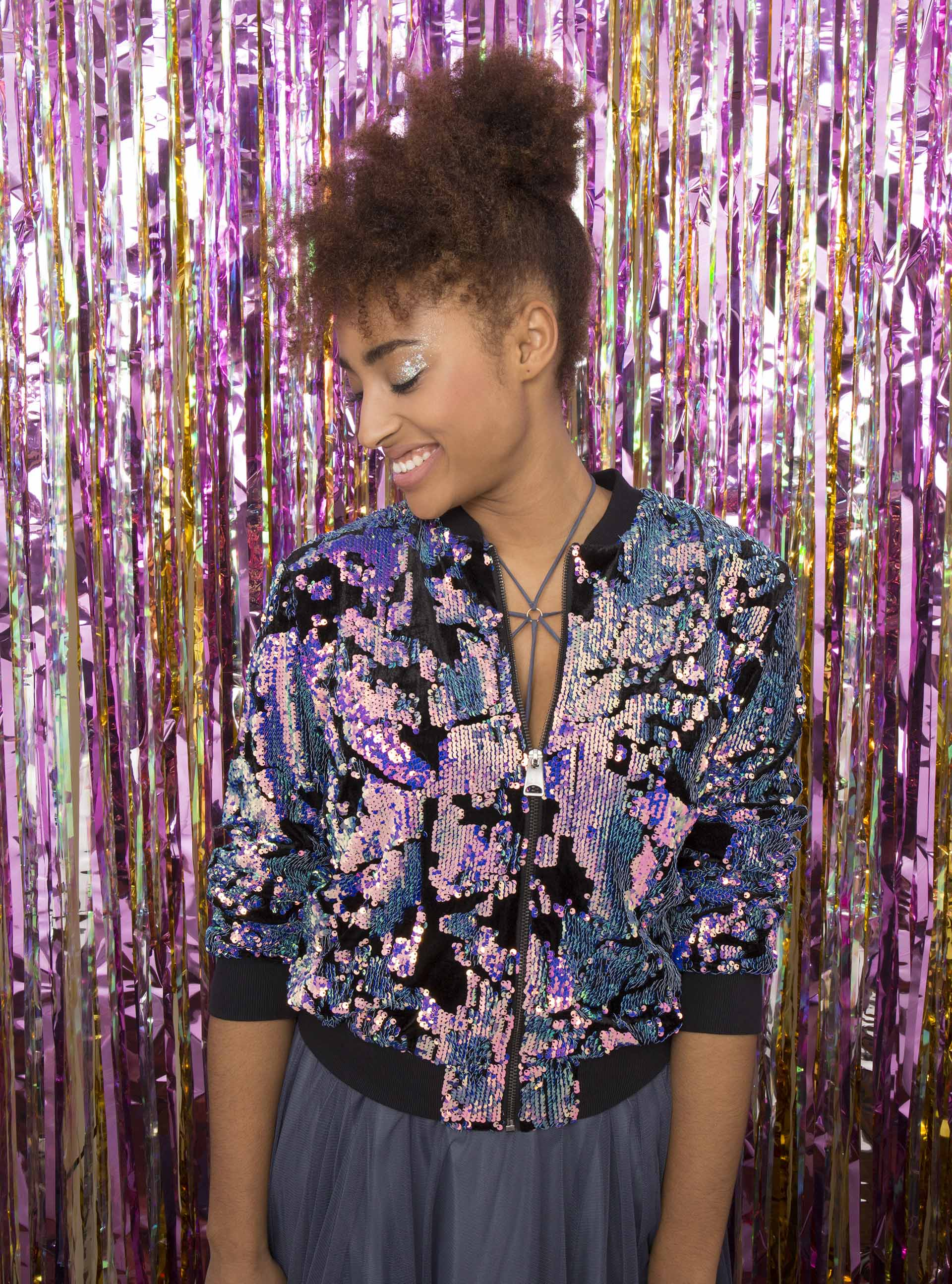 Natural haired model with pinapple updo wearing a floral bomber in front of a party curtain