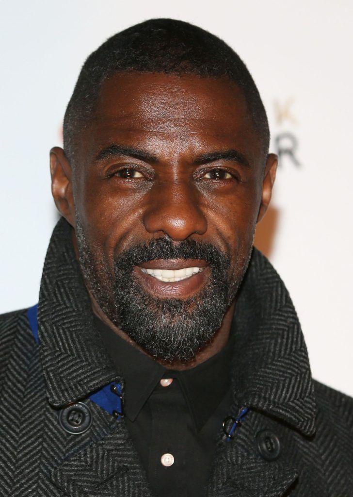 Idris Elba wearing a black shirt with a buzz cut and a beard