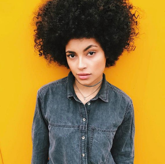 model with natural afro hair wearing denim
